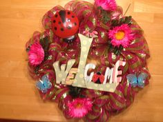 Spring wreath in pink stripe poly deco mesh. With welcome sign, flowers, ladybug, and butterflies.  I took pic before things were wired on, so wreath is laying on the craft table.