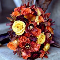 Bouquet composed of Conga, Tropical Amazon and Black Bacara Roses with Mango Calla Lilies, Leucodendron 'Safari Sunset', and Brown Cymbidium.