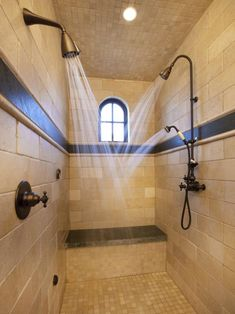 Two fixed bronze showerheads and one hand-held nozzle accommodates up to two people at the same time in this shower covered in tumbled tile.