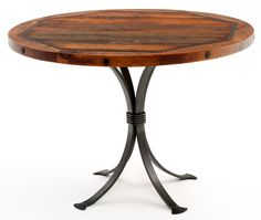 This hand made round reclaimed aged wood dining table has a thick forged metal base to form a unique western, south western, ranch style dinette design. Custom