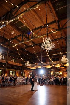 wedding reception first dance at bay 7, american tobacco campus with chandeliers and strung lights photo by brian mullins photography