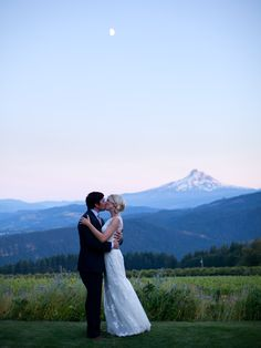 The moon, a mountain, meadow flowers and an adorable couple.  Great photo by Mastin Studio