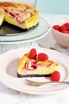 Delicious, super creamy white chocolate and raspberry cheesecake with raspberry sauce