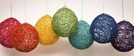 Soak colored yarn in a glue/water mixture (equal parts), wrap around a balloon. Pop the balloon once dry.