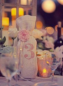 Stencilled wine bags make unexpected table numbers, and you can either serve or give away the wine. Use burlap for a rustic look, or linen if your event is more tailored.