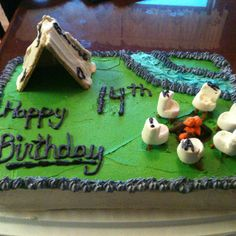 Camping theme birthday cake. The tent is graham crackers covered with white almond bark. The fire is pretzel sticks dipped in chocolate with orange frosting on the tips for flames. The chairs are marshmallows with a notch cut out and pretzel sticks for legs.
