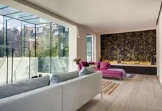 Uno sguardo al salotto posto al primo piano, con ampie vetrate sul giardino privato. Pavimento in parquet di Element 7, un'opera d'arte originale alla parete e il divano Charles disegnato da Antonio Citterio per B&B Italia