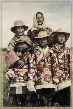 Tibetan family poses in cowboy hats - the mum's idea for bringing in money for the family in the form of baksheesh.