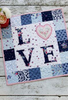 I can't resist making mini quilts! These little cuties are so fun to sew together and they make such cute decor. This Floral LOVE Mini Quilt is great for Valentine's Day – but it's not so cutesy that Quilting For Beginners, Quilting Tutorials, Quilting Projects, Sewing Projects, Small Quilts, Mini Quilts, Baby Quilts, Heart Quilts, Mini Quilt Patterns