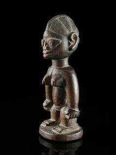 """31 Figur, """"ibeji"""" Yoruba, Nigeria H 25 cm.   Provenienz: Schweizer Privatsammlung, Zürich.  Über Zwillinge wurde schon immer gerätselt: Vergöttert oder verteufelt, in Legenden und Mythen, ja sogar in der Astrologie finden wir die Paare als Ausdruck der Faszination, die von ihnen ausgeht. So auch bei den Yoruba im Südwesten Nigerias, welche nachweislich die weltweit höchste Zwillingsgeburtenrate für sich beanspruchen können."""
