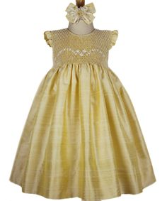 As delicate as rose petals, this beautiful special occasion gold smocked sleeveless dress of pure silk is adorned with hand embroidered silk roses and pearls. There is silk covered buttons and a long sash to put the finishing touch on the back. This very exquisite dress will look divine on your little girl! Fully lined.