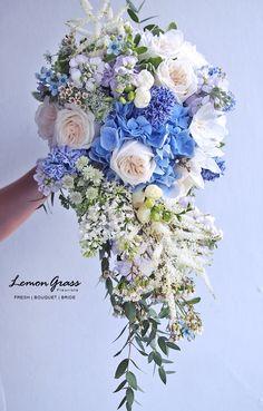 Pretty Cascading Wedding Bouquet Showcasing: Blue Hydrangea, Blue Hyacinth, Lavender Stock, White Astrantia, White Freesia, White Astilbe, White Lilac, Cream Garden Roses