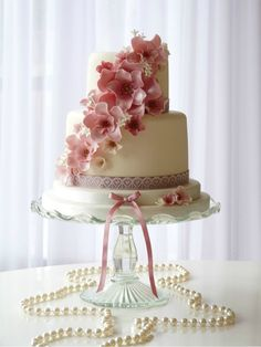 Love the simple but elegant design on this wedding cake.  The way the pink flowers drape across the cakes is so pretty.