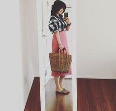 チェックシャツにピンクのスカート かごバッグ