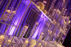 Crystal stage design  with floating candles and touches of purple lighting. #flowers #wedding #stage #ceremony