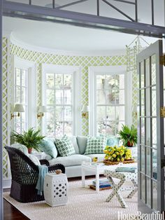 Green hues and latticework create a garden feel in a sunroom. Design: Ashley Whittaker.
