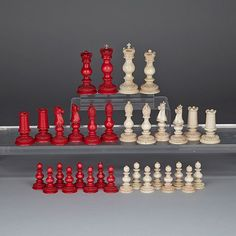 "ASIAN FOR THE ENGLISH MARKET TURNED AND CARVED IVORY CHESS SET, 19TH CENTURY one side stained red, each piece with fine foliate scrolllwork base, the kings and queens with Imperial State Crown of Great Britain, bishops with split miter, knights with horse heads and rooks as turrets, height 4"" - 10.2 cm"