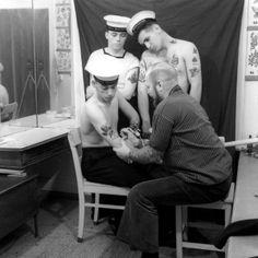 """Marinheiros canadenses a bordo do porta-avião Bonaventure são tatuados em foto feita em 1966. A imagem faz parte da mostra """"Tatoueurs, tatoués"""" (Tatuagem, tatuado, em tradução livre), que traz imagens e esculturas relacionadas a mais de 5.000 anos de história relacionada à arte da tatuagem, no Musée Du Quai Branly, em Paris, na França. A exposição, iniciada este mês e que vai até o dia 18 de outubro de 2104, Foto: Herbert Hoffman/Musée Du Quai Branly"""
