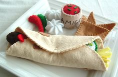 A tortilla wrap filled with mince, cheese, cucumber, tomato and peppers. With a side of corn chips, sour cream and salsa dip. 2 chiilis for decoration