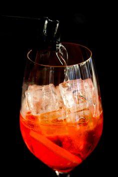 Spritz Le viscontien En allemand, il signifie «pulvériser» ou «éclabousser». Originaire de Venise, au XIXesiècle, quand la Sérénissime faisait encore partie de l'Empire austro-hongrois, ce cocktail fait fureur chez nous au point d'avoir détrôné l'inamovible mojito!  • Un verre à pied • Des glaçons • Un tiers de Campari • Un tiers  de Prosecco • Un tiers d'eau gazeuse  • Une demi-tranche d'orange  • Versez et mélangez les ingrédients directement dans le verre.