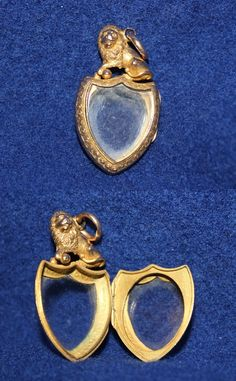 A double-sided gold or gold-plated locket with a very sculptural lion on top.  Possibly Victorian, but probably Edwardian.