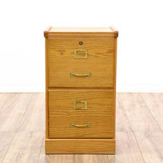 This filing cabinet is featured in a wood with a glossy oak veneer. This traditional style vertical file cabinet has 2 spacious drawers and brass plated handle pulls. Perfect for storing paperwork! #americantraditional #storage #filecabinet #sandiegovintage #vintagefurniture