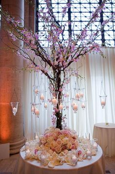 A tree draped in pink orchids is hung with candles and surrounded with pink and white roses.