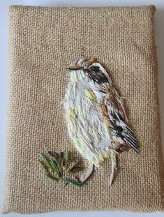 A hand stitched Aquatic warbler, stitched in detail using embroidery thread onto thick hessian fabric. The fabric is wrapped around a canvas and securely fixed to the back of it using heavy duty staples. It measures 5.5 inches across by 7 inches down and is 0.75 inches thick.