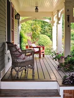 Simple furniture and decor let the porch's architecture and garden views stand out. A collection of potted plants along the perimeter adds a nod to nature.