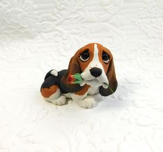 Basset Hound lover Gift, Basset Hound art, Basset Hound Sculpture Polymer Clay with Rose Mini by Raquel at theWRC. Basset Hound lover Gift, Basset Hound art, Basset Hound Sculpture Polymer Clay with Rose Mini by Raquel at theWRC This little pup looks so cute holding a a rose in it's mouth for someone special! Hand sculpted polymer clay dog. Made with love and care! Measures approx. 1.75 inches tall x 2.5 inches.
