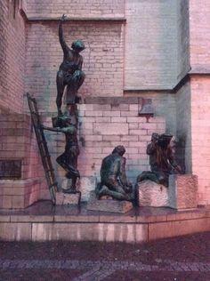 Standbeelden op de voorgrond, muur op de achtergrond