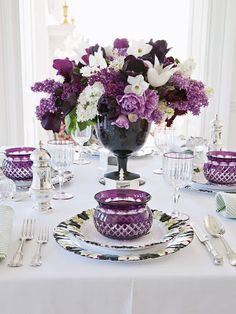 Years of collecting china and vases yield a pretty astounding collection of tabletop patterns. Lilacs and tulips in a full spectrum of purple hues sit in a beautiful glass goblet as a centerpiece. Carolyne Roehm