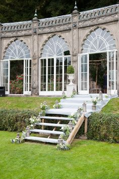 Steps to the ceremony lined with florals - Image by Source Images - Multicultural Hindu & English wedding with traditional sari dress for a classic orangery reception in the Cotswolds with a Black Cab Photo Booth.
