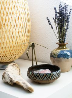 """My bedside table holds a table lamp made of bamboo, a vintage bowl and brass crane figurine, a vintage vase with dried lavender and a piece of driftwood brought home from a trip to the French Atlantic coast."" #vignette"