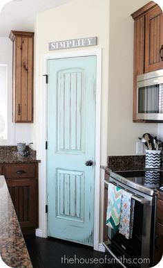 Painted blue door on the pantry. What a fantastic pop of color for a kitchen!