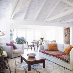 A fresh coat of white paint brightens brick walls and a wood-paneled ceiling, making a living space appear larger and more relaxed   domino.com/natural-beauty. Design by Lauren Soloff and Chay Wike #Padgram