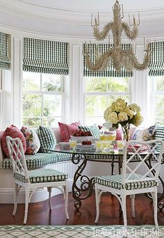 Pretty beach cottage window seat breakfast area in fresh green and white with pops of pink - Traditional Home®