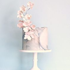 Modern masterpieces jasmine rae wedding cakes bas relief stone wrapped in torn silver edged fondant topped with a sprig of soft pink flowers part of a duo for a desserttable pics coming soon mightylinksfo