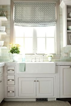 I LOVE THIS! Design Galleria  ~Ivory kitchen cabinets with glass subway tiles backsplash, stainless steel curved front apron sink, marble countertops and Boston Functional Library Wall Light.