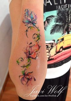 Flowers decorate this girls arm from wrist to elbow in a watercolor tattoo by Javi Wolf