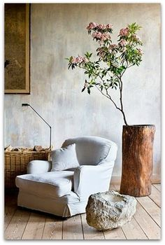 Indoor flowering tree branch + white slipcovered accent chair + neutral and wabi sabi