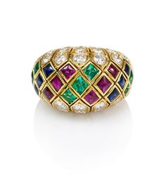 A gold, and diamond ring of bombe design set with a harlequin pattern of buff top rubies, sapphires and emeralds, in 18k. Atw of diamonds: 2.92 carats, VVS2/VS, H. Atw of other stones: 3.45 carats. Cartier, France #650899.  	      	  Circa:  	  1965