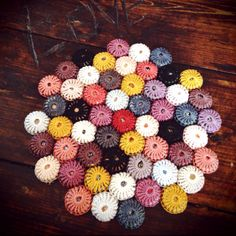Bottle cap trivet...There's gotta be some way to do this by spray painting the bottle caps and then gluing them together