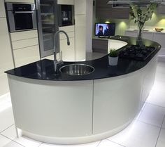 Gloss Ivory kitchen island with large curved units and black glass worktop. For more gloss kitchen ideas, please see http://www.sheratonkitchens.co.uk/kitchens?finish%5B%5D=Gloss