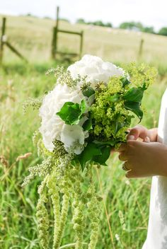 Countryside wedding bouquet of white hydrangea, alchemilla mollis (lady's mantle), green amaranthus (love lies bleeding) in whites and greens. Wedding flowers by London based Floral designers Okishima & Simmonds. www.okishimasimmonds.com