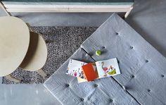 Blick auf eine Matratze auf dem Fußboden, daneben ein Couchtisch und Sofa