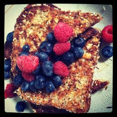 """French toast was never so healthy!  """"sprouted wheat bread dipped in egg and almond milk, coated with shredded coconut, sesame and chia seeds, and sliced almonds. Cooked in coconut oil. Berries and maple syrup drizzle on top"""