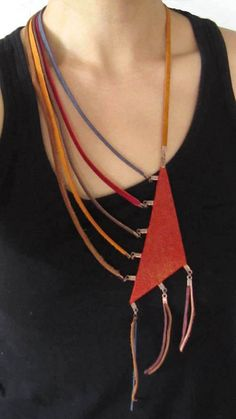 Delightfully different assymetrical leather necklace with bronze metal connectors. Center triangle piece is a deep red and gold speckled leather material attached by a mixed color of leather and suede strands. A carefree fashion piece that will go with any pair of jeans, casual wear,
