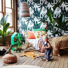 Very eclectic bohemian kids room! Palm leaf wallpaper plus wicker bed