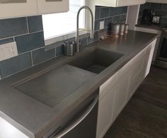 Concrete countertop with integrated sink and drainboard. www.kingsmenconcrete.com